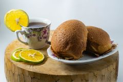 2 коричневых хлеба на плите и одной чашке теплого чая лимона помещены на деревянной циновке с изолированной белой предпосылкой стоковые фотографии rf