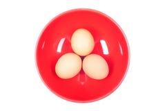 3 коричневых яичка в красной плите на белизне изолировали предпосылку верхний v Стоковое Фото