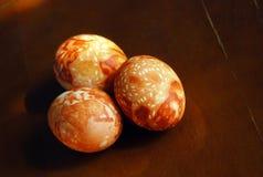 3 коричневых яичка пасхи покрашенных вручную на коричневой таблице Стоковое Фото
