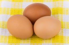 3 коричневых яичка цыпленка на желтой скатерти Стоковое фото RF