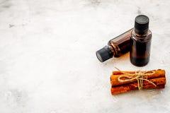 Коричное масло для варить, aromatheraphy, забота кожи Бутылки около ручек циннамона на сером космосе предпосылки для текста Стоковые Фотографии RF