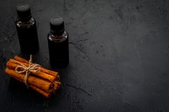 Коричное масло для варить, aromatheraphy, забота кожи Бутылки около ручек циннамона на черном космосе предпосылки для текста Стоковое Изображение RF
