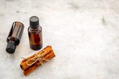 Коричное масло для варить, aromatheraphy, забота кожи Бутылки около ручек циннамона на сером космосе предпосылки для текста Стоковые Изображения RF