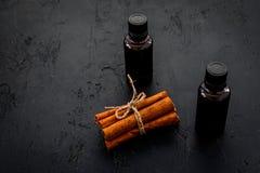 Коричное масло для варить, aromatheraphy, забота кожи Бутылки около ручек циннамона на черном космосе предпосылки для текста Стоковая Фотография