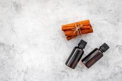 Коричное масло для варить, aromatheraphy, забота кожи Бутылки около ручек циннамона на сером космосе предпосылки для текста Стоковая Фотография