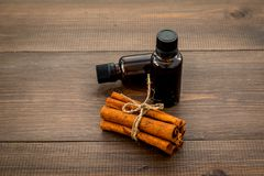 Коричное масло для варить, aromatheraphy, забота кожи Бутылки приближают к ручкам циннамона на темной деревянной предпосылке Стоковое Изображение RF