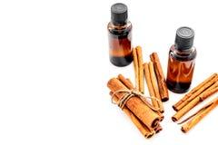 Коричное масло для варить, aromatheraphy, забота кожи Бутылки приближают к ручкам циннамона на белом космосе взгляд сверху предпо Стоковые Изображения RF