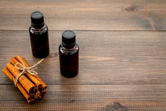 Коричное масло для варить, aromatheraphy, забота кожи Бутылки приближают к ручкам циннамона на темном деревянном космосе предпосы Стоковое Изображение RF