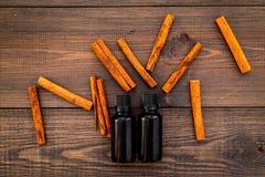 Коричное масло для варить, aromatheraphy, забота кожи Бутылки приближают к ручкам циннамона на темном деревянном взгляд сверху пр Стоковая Фотография RF