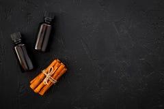 Коричное масло для варить, aromatheraphy, забота кожи Бутылки приближают к ручкам циннамона на черном космосе взгляд сверху предп Стоковые Фото