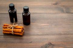 Коричное масло для варить, aromatheraphy, забота кожи Бутылки приближают к ручкам циннамона на темном деревянном космосе предпосы Стоковые Изображения