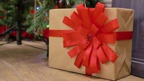 Коробка в бумаге kraft, связанной с красной лентой, со смычком, рядом с рождественской елкой сток-видео