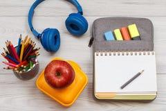 Коробка для завтрака, яблоко, карандаши, наушники и открытая книга тренировки дальше Стоковое Фото