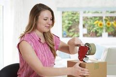 Коробка запечатывания женщины дома для отправки Стоковая Фотография