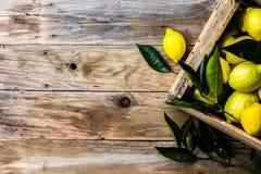 Коробка лимонов с свежими листьями на деревянной предпосылке с космосом экземпляра Взгляд сверху Стоковое Изображение RF