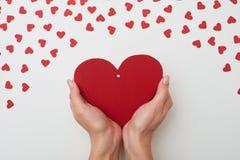 Коробка красного цвета присутствующая в форме сердца в руках женщины Стоковое фото RF