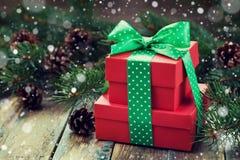 Коробка красного цвета присутствующая с украшением ленты смычка конуса ели и хвои с волшебным влиянием снега на деревянной дереве Стоковое Изображение