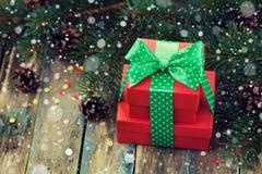 Коробка красного цвета присутствующая с украшением ленты смычка конуса ели и хвои с волшебным влиянием снега на деревянной дереве Стоковая Фотография