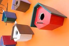 Коробка красочного гнезда птицы деревянная украшенная на оранжевой стене Стоковые Изображения