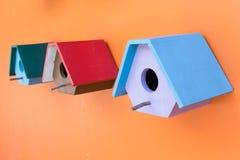 Коробка красочного гнезда птицы деревянная украшенная на оранжевой стене Стоковая Фотография