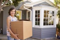 Коробка нося женщины в новый дом на Moving день Стоковые Изображения
