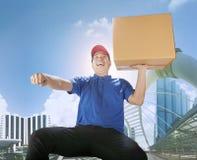 Коробка нося карточки работника доставляющего покупки на дом с эмоцией haapiness в бушеле города Стоковая Фотография RF