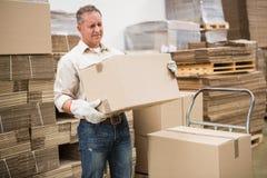 Коробка нося работника в складе стоковые фотографии rf
