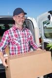 Коробка нося счастливого работника доставляющего покупки на дом в передней тележке Стоковые Изображения