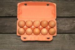 Коробка органических коричневых яичек на деревянной доске Взгляд сверху Стоковое фото RF