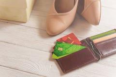 Коробка, открытый бумажник, кредитные карточки и ботинки женщины лежа на белой деревянной предпосылке Стоковые Фотографии RF