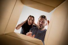 Коробка пар распаковывая и раскрывая коробки и смотря внутрь Стоковое Фото