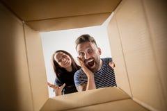 Коробка пар распаковывая и раскрывая коробки и смотря внутрь Стоковое Изображение