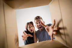 Коробка пар распаковывая и раскрывая коробки и смотря внутрь Стоковые Изображения