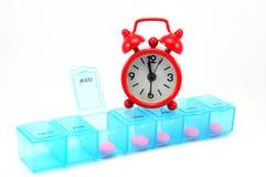 Коробка пилюльки Dialy и красные часы на белом blackground Стоковая Фотография RF