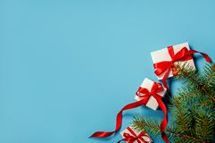 Коробка подарка рождества белая с красной лентой на голубых ветвях ели предпосылки на космосе экземпляра голубой предпосылки плос стоковое изображение rf