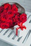 Коробка подарка и красные розы Настоящий момент на день валентинки для женщины Стоковое фото RF
