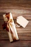 Коробка подарка на деревенской деревянной таблице с пустой биркой Стоковые Изображения