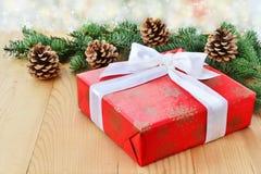 Коробка подарка рождества красная с белыми смычком, ветвями ели и конусами Стоковое фото RF