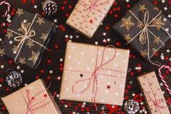 Коробка праздничного подарка рождества на украшенной праздничной таблице с конусами сосны и звездами искры Стоковые Фотографии RF