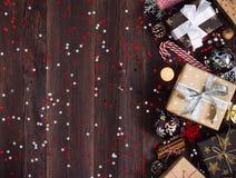 Коробка праздничного подарка рождества на украшенной праздничной таблице с шариком свечи тросточки конфеты конусов сосны Стоковое фото RF
