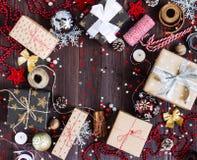 Коробка праздничного подарка рождества на украшенной праздничной таблице с шариком свечи тросточки конфеты конусов сосны Стоковое Фото