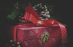Коробка праздничного подарка украшенная с красной лентой, конусами сосны, отрубями ели стоковые изображения rf