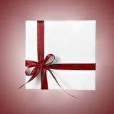 Коробка праздника присутствующая белая с красной лентой на предпосылке градиента Стоковое фото RF