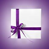 Коробка праздника присутствующая белая с фиолетовой розовой лентой на предпосылке градиента Стоковые Изображения