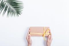 Коробка праздничного подарка с лентой в руках и ладони женщин Стоковое Изображение RF