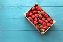 Коробка плодоовощ клубник сезонная на голубой деревянной предпосылке Стоковая Фотография