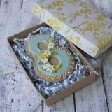 Коробка с печеньем покрытым с голубой поливой сделанной в форме 8 с daffodils и мимозой на белое деревянном стоковые изображения rf