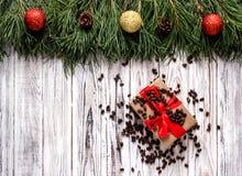 Коробка с подарком для Нового Года и рождества с гайками сосны на белой деревянной предпосылке, елевыми ветвями с шариками рождес стоковое фото rf