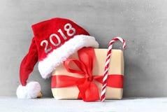Коробка с подарком на рождество и шляпа santa на серой предпосылке Стоковое Фото