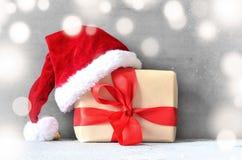 Коробка с подарком на рождество и шляпа santa на серой предпосылке Стоковые Изображения